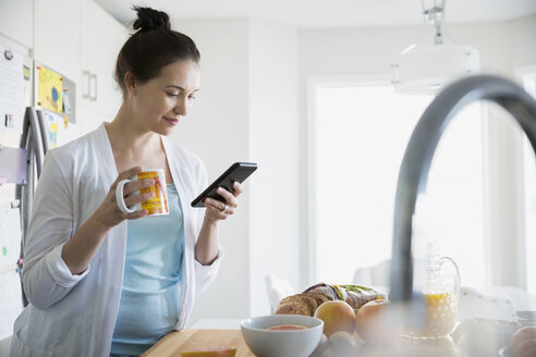 Woman in pajamas drinking morning coffee and texting - HEROF21646