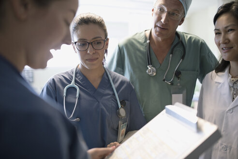 Surgeon, doctor and nurses discussing medical record in hospital - HEROF21736