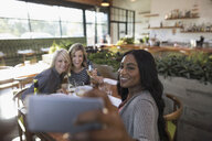 Smiling women friends taking selfie with camera phone, dining at restaurant table - HEROF21769