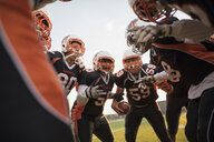 Teenage boy high school football team talking in huddle on football field - HEROF21781