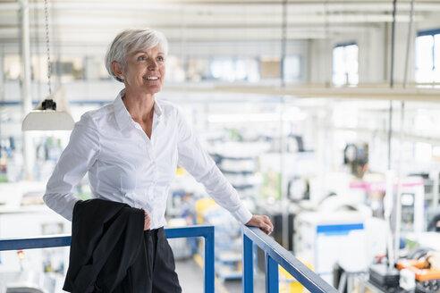 Smiling senior businesswoman on upper floor in factory overlooking shop floor - DIGF05731