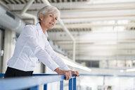 Senior businesswoman on upper floor in factory overlooking shop floor - DIGF05734