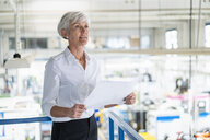 Senior woman holding plan in a factory - DIGF05737