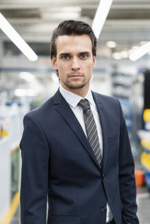 Portrait of confident businessman in a factory - DIGF05749