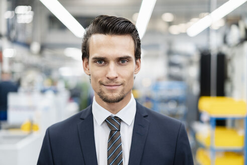 Portrait of confident businessman in a factory - DIGF05752