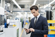 Businessman using cell phone in a factory - DIGF05755