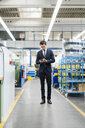 Businessman using cell phone in a factory - DIGF05758
