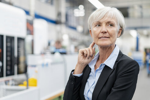 Portrait of senior businesswoman in a factory looking around - DIGF05761