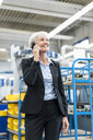 Smiling senior businesswoman on cell phone in a factory - DIGF05764