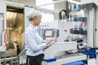 Senior businesswoman using tablet in a factory - DIGF05779
