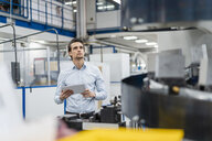 Businessman holding tablet and looking at a machine in a factory - DIGF05794