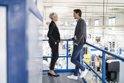 Smiling businessman and senior businesswoman talking in a factory - DIGF05800