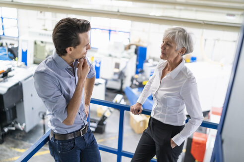 Businessman and senior businesswoman talking in a factory - DIGF05812