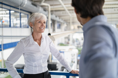 Businessman and senior businesswoman talking in a factory - DIGF05815