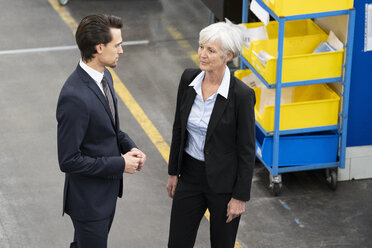 Businessman and senior businesswoman talking in a factory - DIGF05818