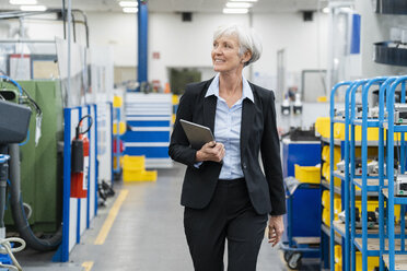 Senior businesswoman with tablet walking in a factory - DIGF05821