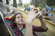Teenage girl relaxing, texting with cell phone in hammock at outdoor school campsite - HEROF21807