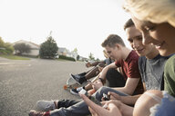 Teenage friends hanging out, texting with cell phones on sunny street curb - HEROF21831