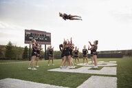 Teenage girl high school cheerleading team performing on football field - HEROF21870