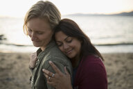 Tender, affectionate, serene lesbian couple hugging on ocean beach - HEROF21879