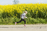 Profile view of girl running on dirt road at rapeseed field - ASTF02817