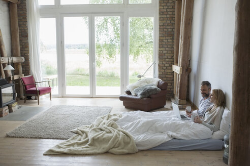 Couple drinking coffee and using laptop in bed mattress on bedroom floor - HEROF21906