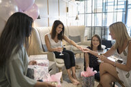 Bride-to-be showing wedding ring to bridesmaid friends celebrating bridal shower in nail salon - HEROF21996
