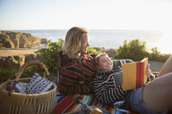 Affectionate couple reading book, relaxing on sunny beach - HEROF22023