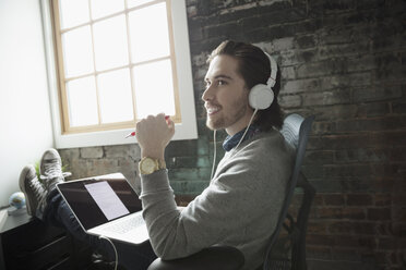 Smiling creative businessman with laptop listening to music with headphones and feet up in office - HEROF22077