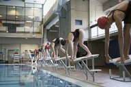 Young women swimmers ready, standing on starting platforms at swimming pool - HEROF22095