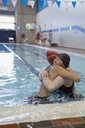Smiling young women swimmers hugging in swimming pool - HEROF22104