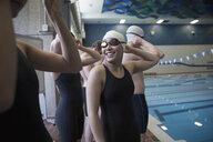 Smiling teenage girl swimmer talking to teammate at swimming pool - HEROF22119
