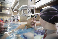 Smiling female swimmers celebrating in swimming pool - HEROF22125