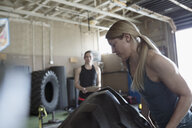 Strong, focused woman lifting tire in crossfit training at gym - HEROF22134