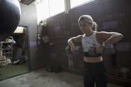 Woman weightlifting with dumbbells in gritty gym - HEROF22143