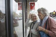 Smiling senior women window shopping at urban storefront - HEROF22182
