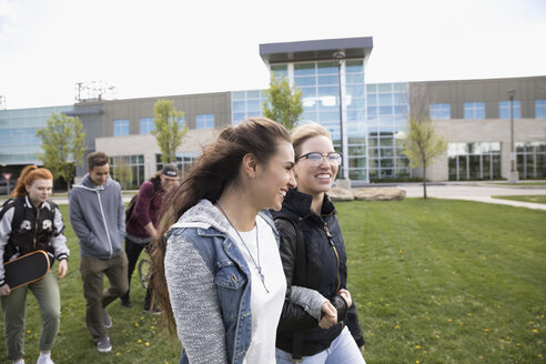 Smiling female college students walking arm in arm on college campus - HEROF22248