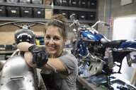 Portrait smiling, confident female motorcycle mechanic fixing motorcycle in auto repair shop - HEROF22296