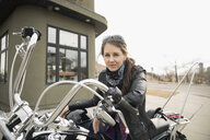 Portrait female biker on motorcycle in parking lot - HEROF22308