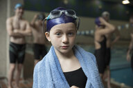 Portrait girl swimmer wrapped in towel at practice - HEROF22350