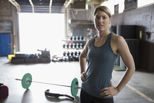 Portrait confident, fit woman resting with hands on hips near barbell in gym - HEROF22356