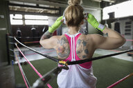 Rear view tattooed woman boxer listening to music with headphones in boxing ring at gym - HEROF22359