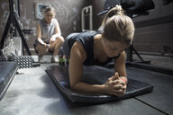Personal trainer timing female client doing plank exercise in gritty gym - HEROF22365