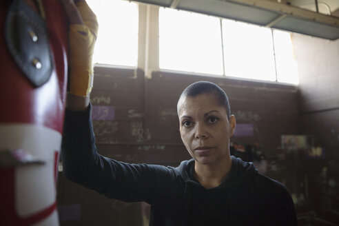 Portrait serious, tough female boxer leaning on punching bag in gritty gym - HEROF22380
