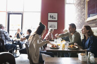 Parents with teenage daughter eating brunch at diner table - HEROF22431