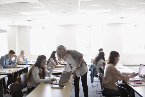 Professor watching college students studying in classroom - HEROF22440