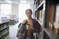 Portrait confident female college student with coffee in library - HEROF22452
