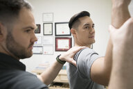 Male physiotherapist examining shoulder and arm of client in office - HEROF22458