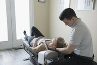 Male physiotherapist examining neck of woman on clinic examination table - HEROF22512