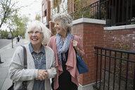 Laughing senior women walking on urban sidewalk - HEROF22611